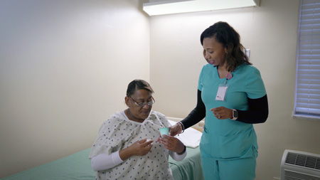 photo of nurse giving medication to senior patient